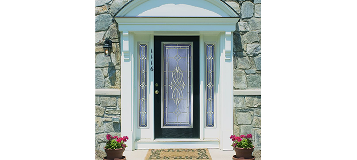 Columned front entry door with side panels and arched wood on top